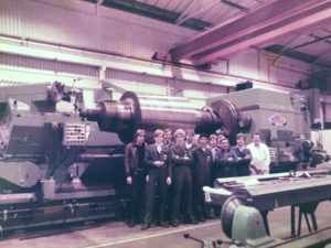 Foreman Vic Markley with apprentices in front of Roll Grinder